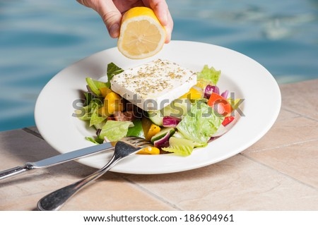 Hand squeezing lemon on feta cheese salad,swimming pool in background.