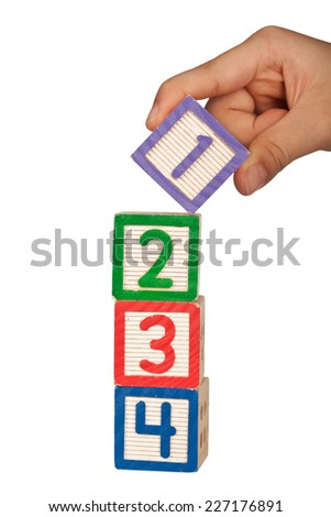 Hand stacking number blocks isolated on white background  - stock photo