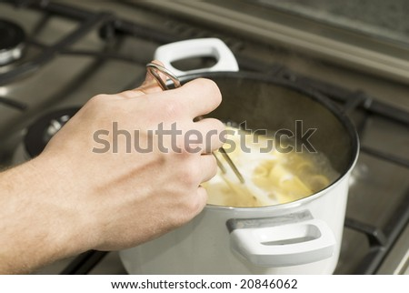 Hand stirring noodles boiling in a pot on top of a stove. Horizontally framed photo. - stock photo