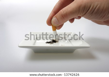 Hand stubbing out a cigarette on white ashtray isolated on white - stock photo