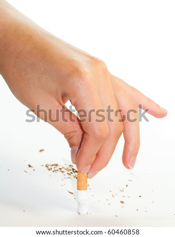 Hand stubbing out a cigarette on white surface isolated - stock photo