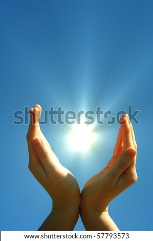 hand sun and blue sky with copyspace showing freedom or solar power concept