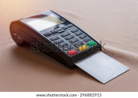 Hand Swiping Credit Card on POS terminal in Store. - stock photo