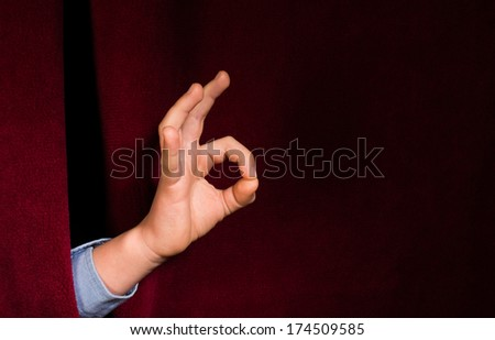 Hand symbol of success. Red curtain background - stock photo