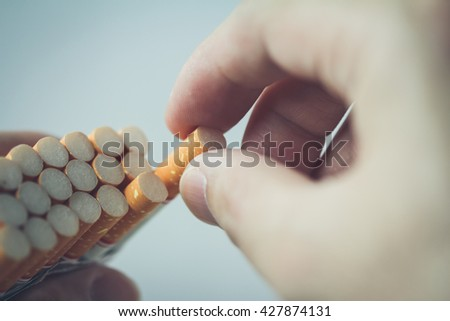 hand take out cigarette from pack - stock photo