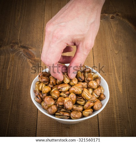 Hand taking a broad  bean from white bowl - stock photo