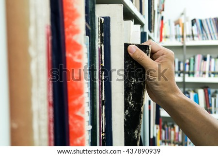 Hand taking book from the shelf in university library - stock photo