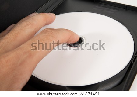 hand taking DVD disc from box. - stock photo