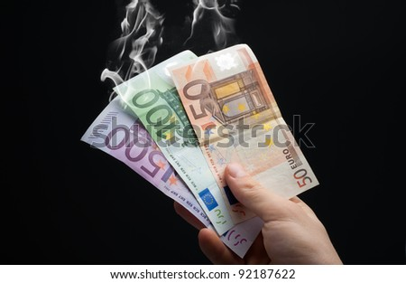 hand taking euros to smoke - stock photo
