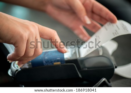 Hand taking receipt from pos terminal - stock photo