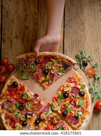 hand taking slices of pizza - stock photo