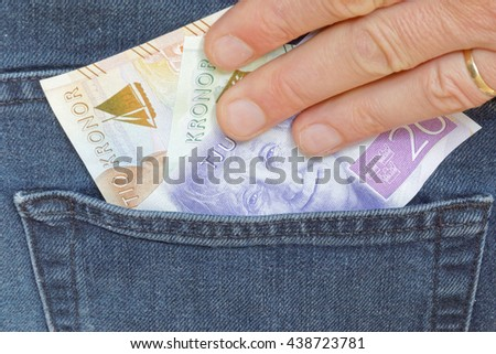 Hand taking swedish bank notes sticking up from a jeans pocket