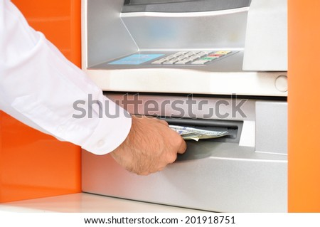 Hand taking (withdraw) money from ATM - stock photo