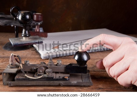 Hand tapping morse code on an antique telegraph machine - stock photo