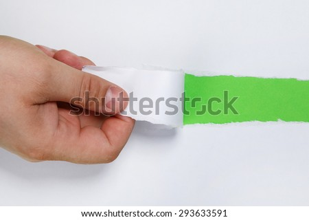 Hand tear a strip of white paper - stock photo