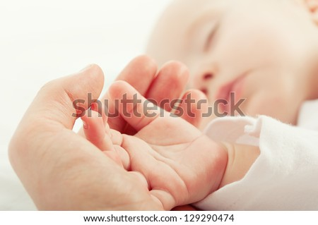 hand the sleeping baby in the hand of mother  close-up