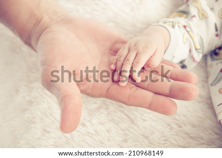 hand the sleeping baby in the hand of mother close-up - stock photo