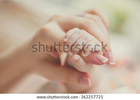 hand the sleeping baby in the hand of mother close-up. Extreme closeup of a baby's hand in mother's finger. Close-up of baby's hand holding mother's finger. Close-up of baby's hand. tenderness - stock photo