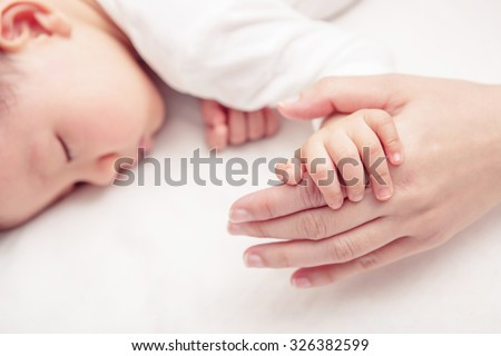 Hand the sleeping baby in the hand of mother close-up (Soft focus and blurry) - stock photo