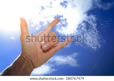 Hand through the deep blue sky, I love you sign and symbol, - stock photo