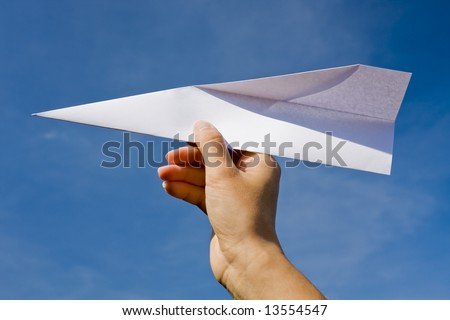 Hand throwing a paper plane - stock photo