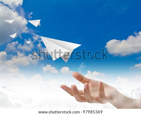 Hand throwing a paper plane in the sky - stock photo