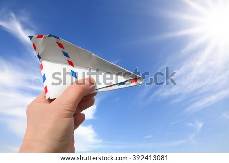Hand throwing a paper plane (made of Post envelope) against beautiful blue sky - stock photo