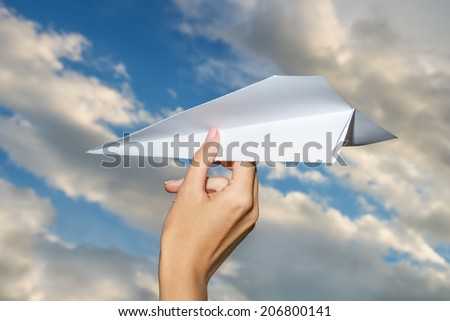Hand Throwing A Paper Plane On Sky - stock photo