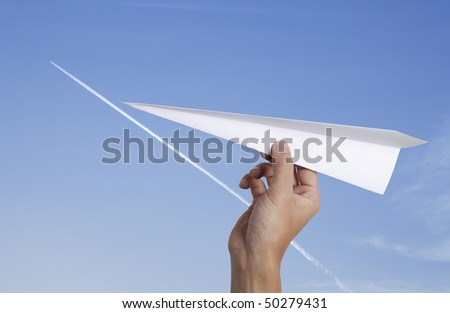 hand throwing a paper plane with jet-steam track on a clear blue sky - stock photo