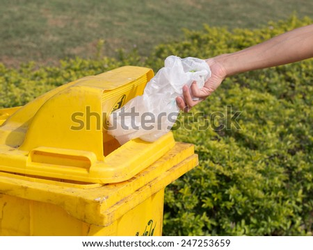 Hand throwing a plastic bag in the yellow bin. - stock photo