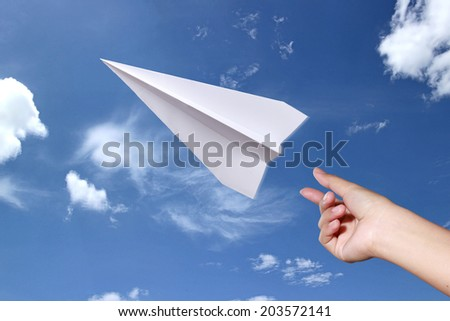 hand throwing airplane paper