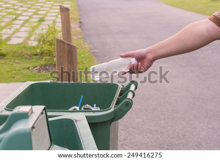 Hand throwing bottle in trash cans - stock photo