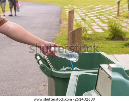 Hand throwing bottle in trash cans. - stock photo