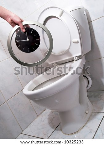 Hand throwing clock per a toilet bowl. Flush time into a toilet, dally away - stock photo