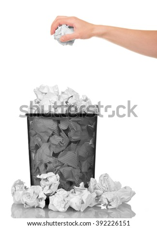 Hand throwing crumpled paper into a metal basket isolated on white background. - stock photo