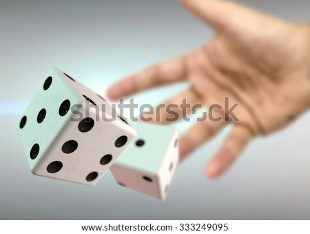 Hand throwing 2 dice at casino with lens flare behind. Board game or gambling. Taking a chance on a bet. - stock photo