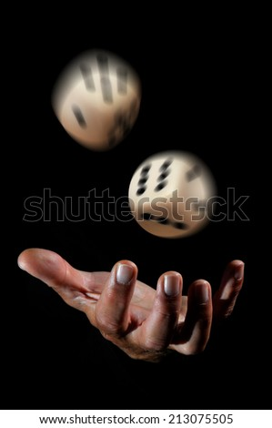 Hand throwing dice in a dark background - stock photo