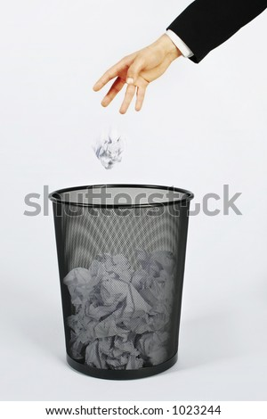 Hand throwing paper in trash. The paper has motion blur on it.