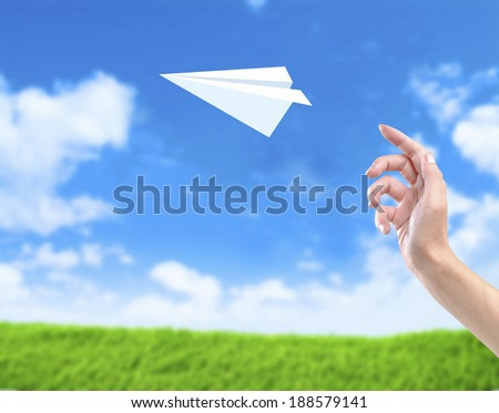 Hand throwing Paper plane against blue sky and green yard