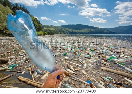hand throwing plastic bottle in beautiful landscape ruined by pollution, bicaz lake, romania - stock photo