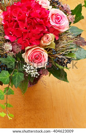 Hand tied bouquet of pink roses and red hortensia flowers with leaves and ivy on a background light wood, copy space, copyspace - stock photo