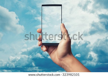 Hand to hold mobile phone on blue sky - stock photo