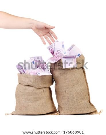 Hand to sacks with euro bills - stock photo