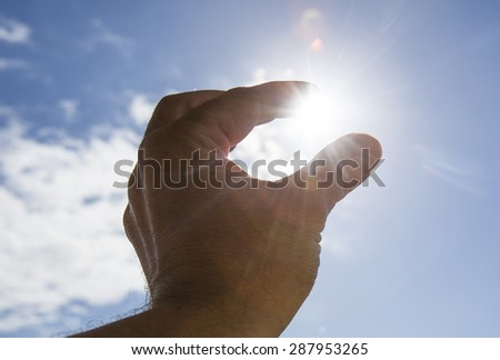 Hand to sun,sun rays passing through fingers,holding sun  - stock photo