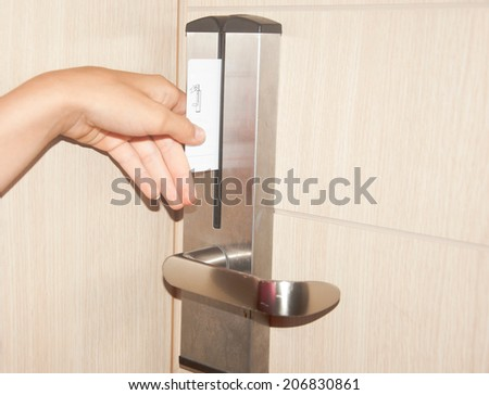 hand touch keycard on hotel door - stock photo