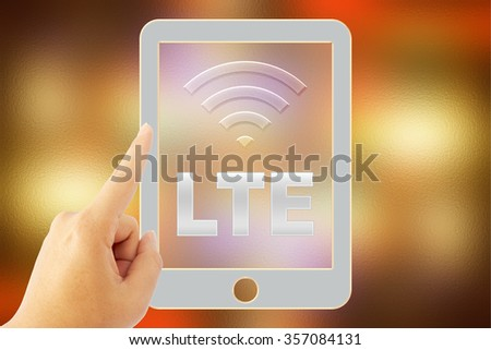 """hand touch tablet """"LTE"""" over blurred background - stock photo"""