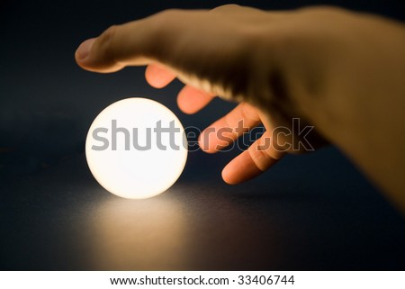 Hand touching a bright ball, Concept of magic - stock photo