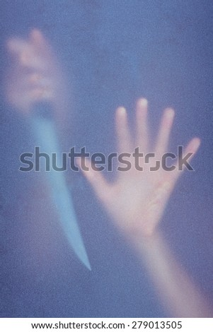Hand touching frosted glass and holding knife in the shadow