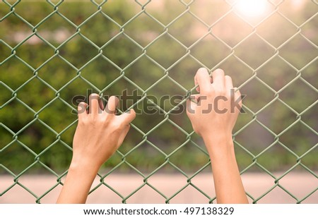 Hand touching iron mesh