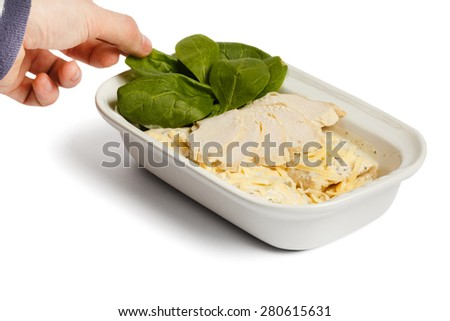 Hand touching spinach. Ham, and cheese in a bowl on a white isolated background - stock photo